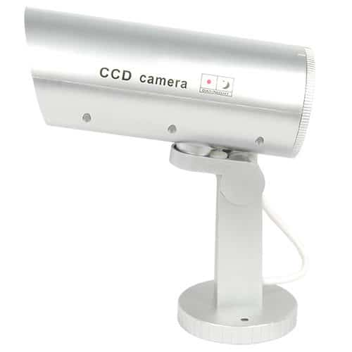 side view of white standing motion activated dummy security camera