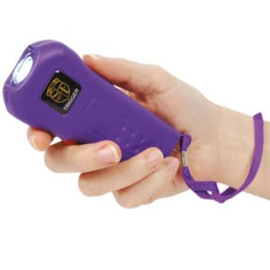 purple trigger stun gun with flashlight in hand